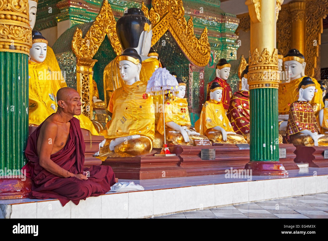Buddhist monk praying in front of Buddha statues in the Shwedagon Zedi Daw Pagoda at Yangon / Rangoon, Myanmar / - Stock Image