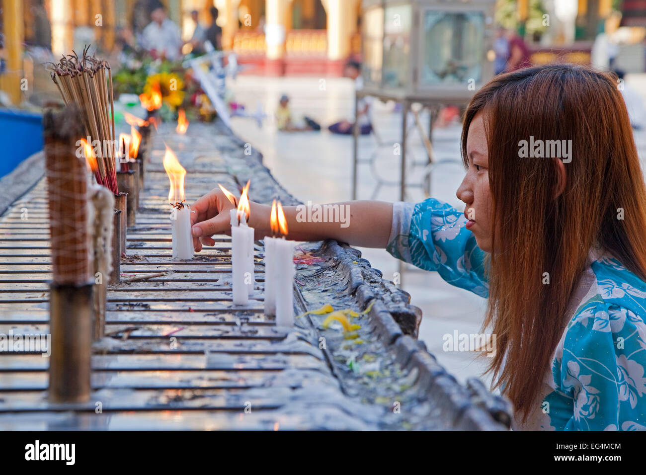 Burmese girl burning candles and incense sticks / joss sticks in the Shwedagon Zedi Daw Pagoda at Yangon, Myanmar - Stock Image