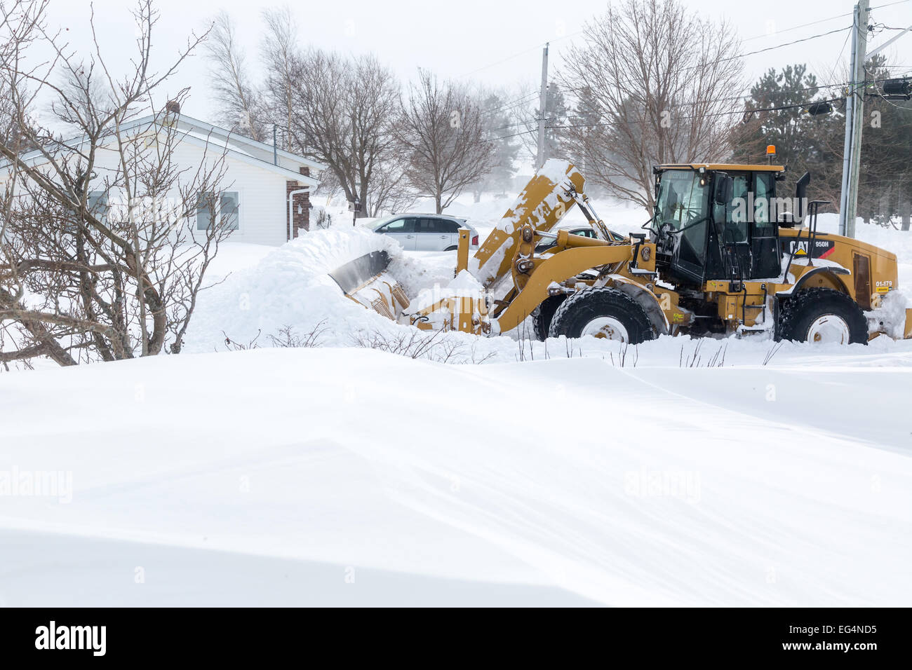 Large snowplow pushes through a heavy snowfall on a suburban street after a snow storm. - Stock Image