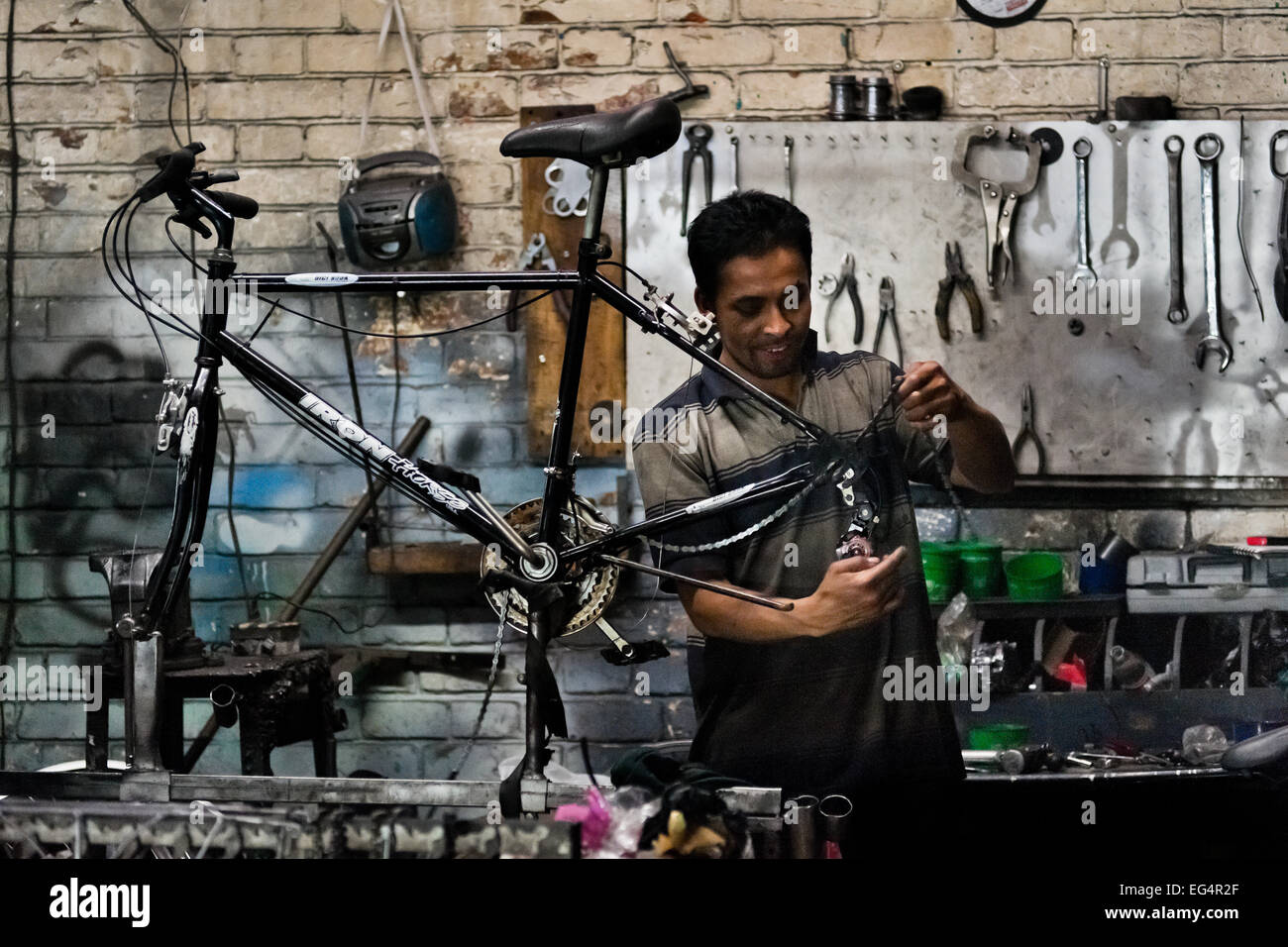 A bicycle mechanic assembles a custom made bike in a small scale bicycle factory in Bogota, Colombia. - Stock Image