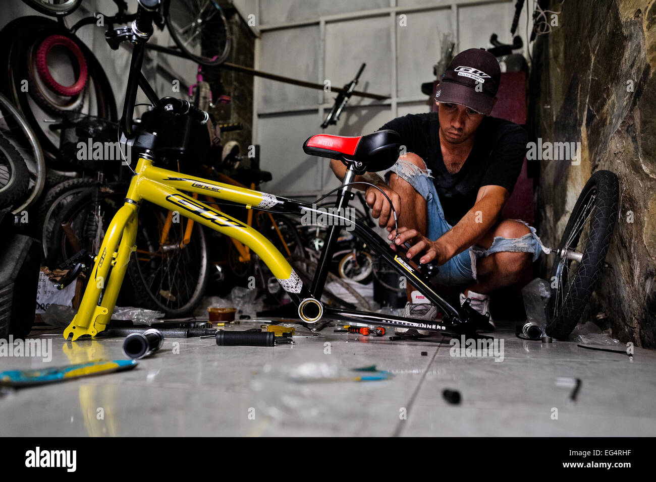 A bicycle mechanic assembles a custom made bike in a bicycle workshop in Cali, Colombia. - Stock Image