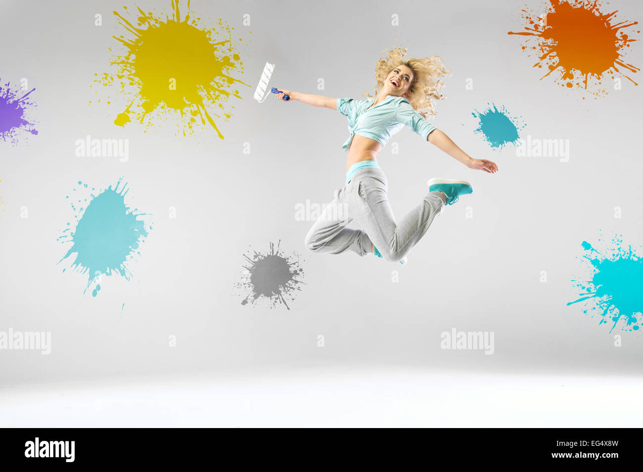 Lady jumping and paiting walls - Stock Image