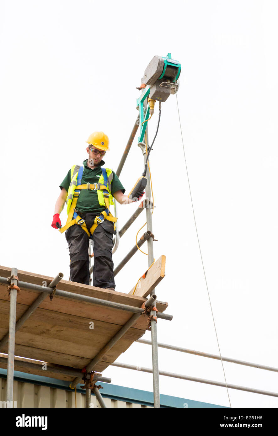 man using hoist and fall restraint harness for safety Stock