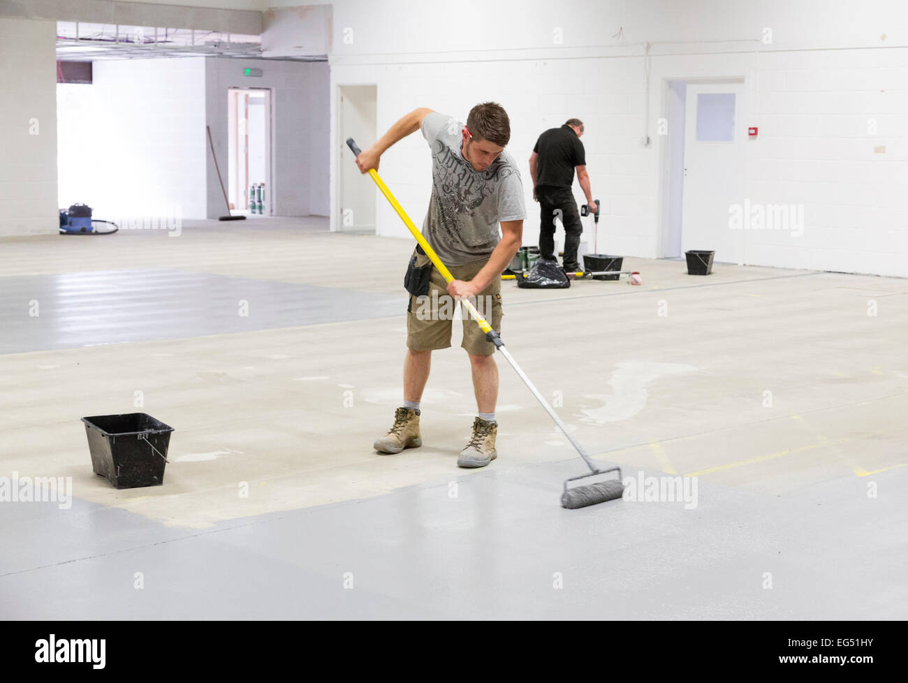 a worker painting a factory floor with epoxy based paint for hard durability - Stock Image