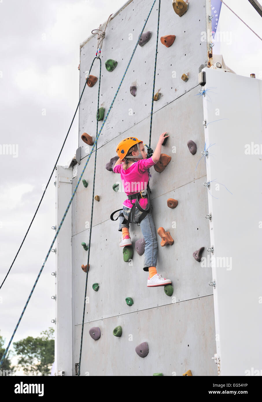 Young girl with safety harness climbing a wall - Stock Image