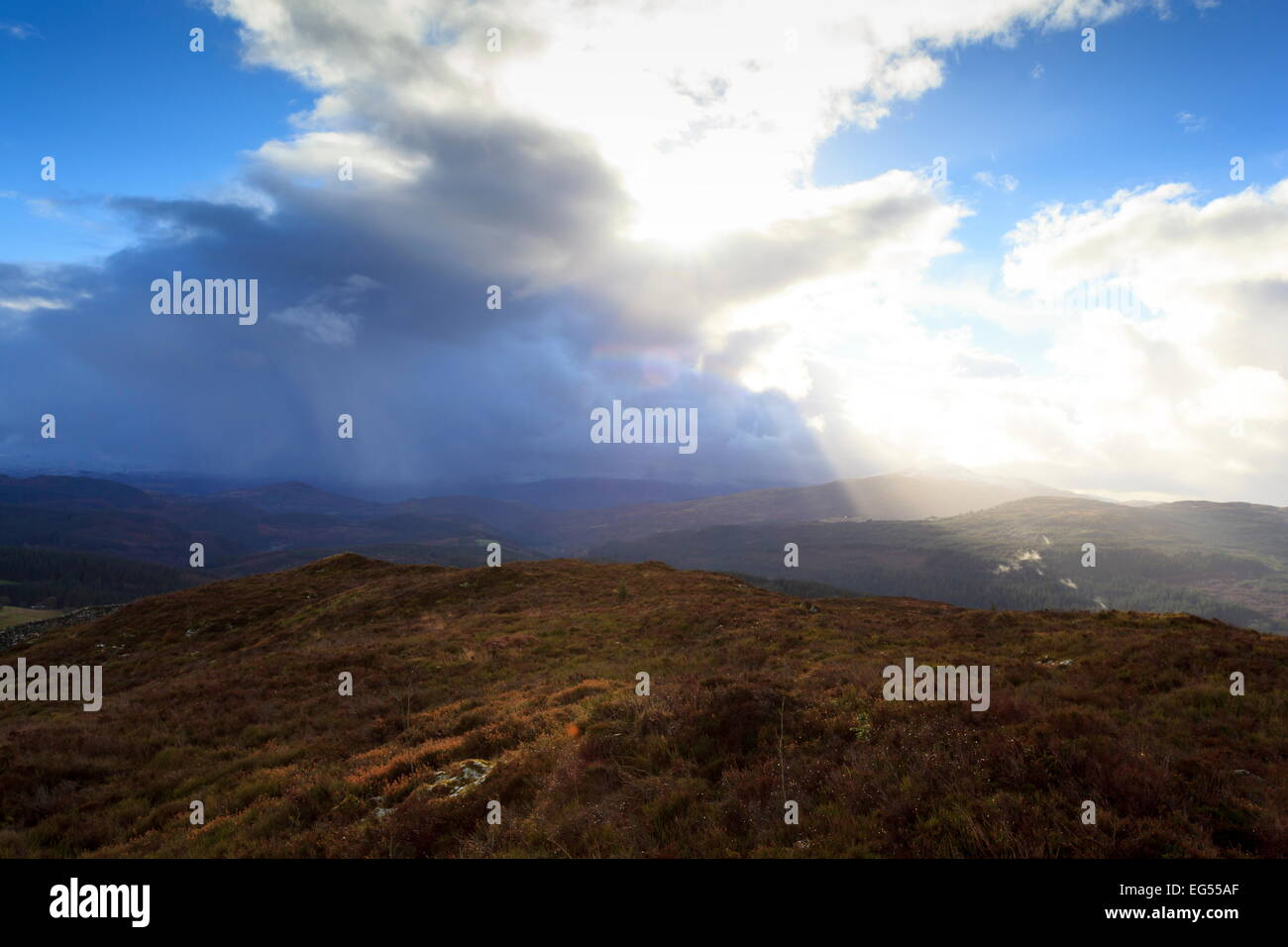 The Sun breaks out from behind the clouds above Coed Y Brenin Forest - Stock Image