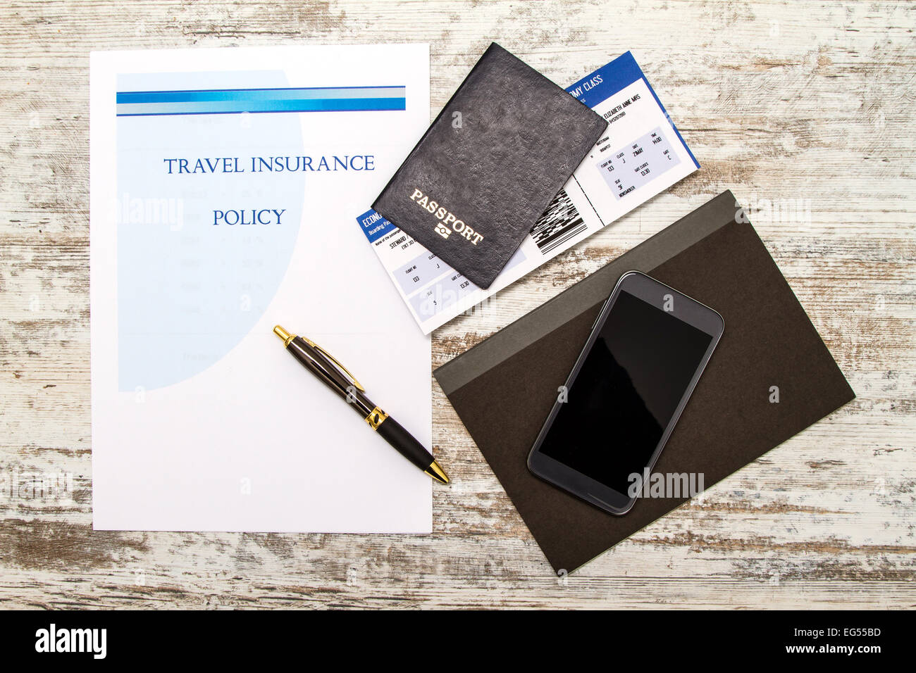 Travel insurance policy booklet with a boarding pass and a passport - Stock Image