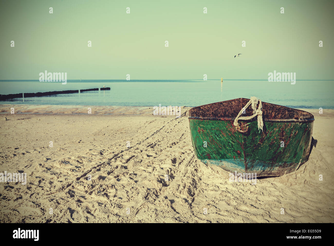 Retro filtered picture of an old rusty steel boat on the beach. - Stock Image