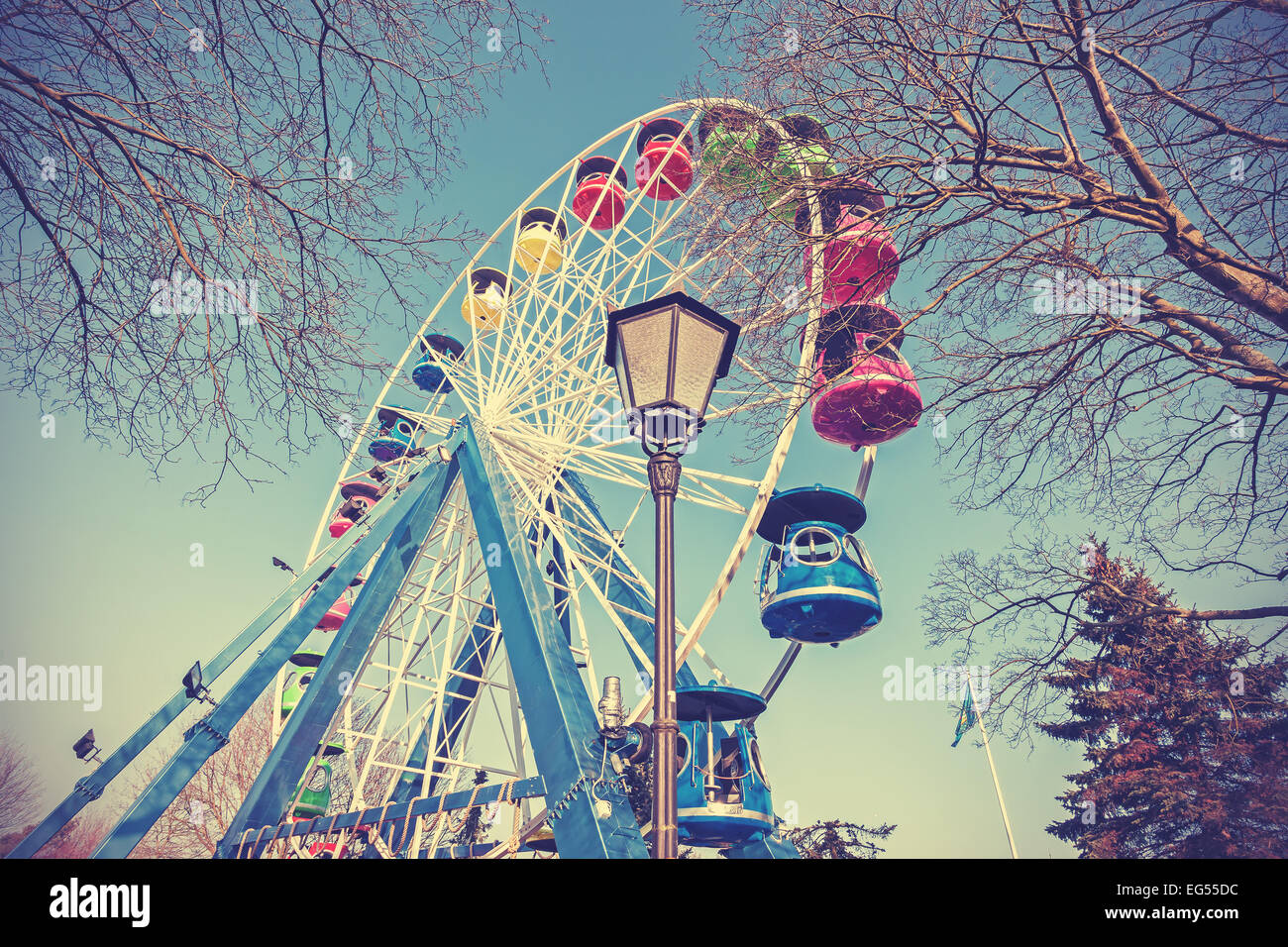 Retro filtered picture of ferris wheel in a park. Stock Photo