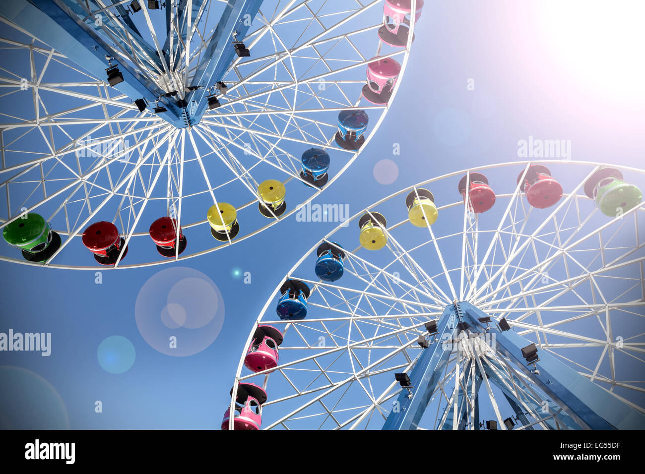 Retro filtered picture of ferris wheels with lens flare. - Stock Image