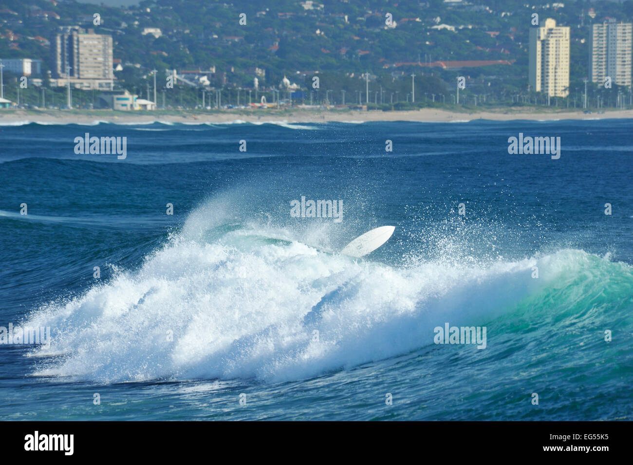 White surfboard flying out of water after surfer wipe-out on breaking wave, bay of Durban, KwaZulu-Natal, South - Stock Image