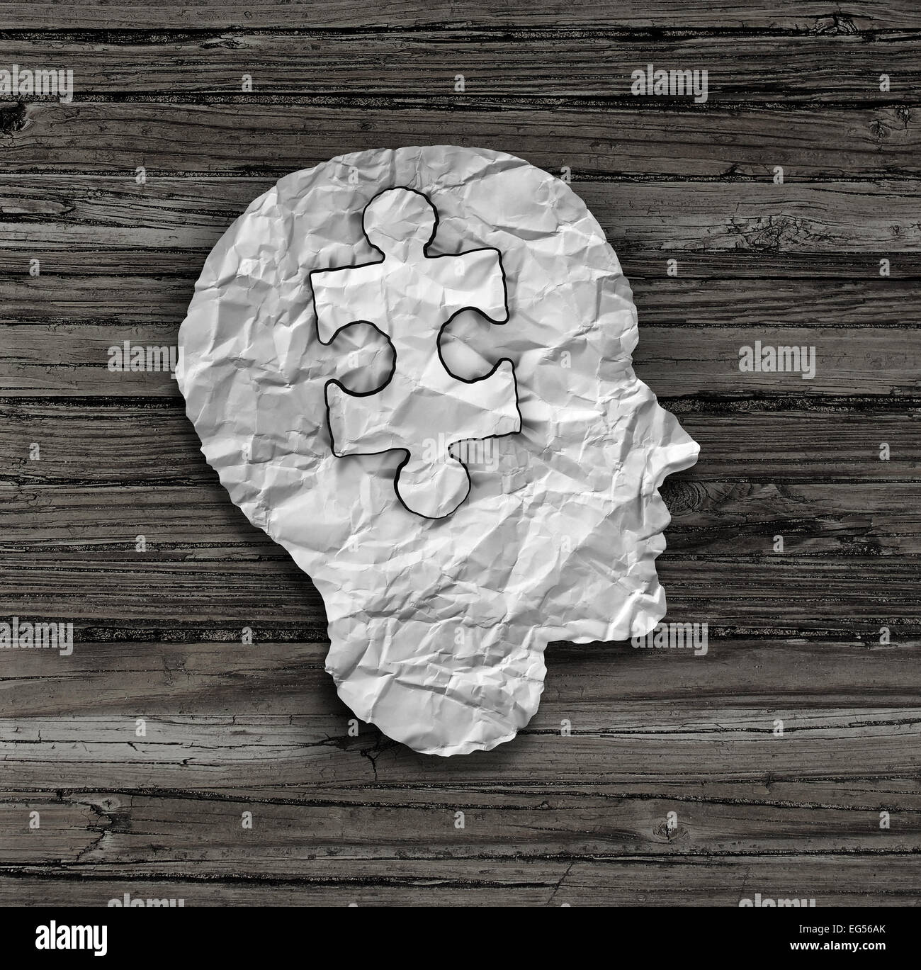 Puzzle head solution concept as a human face profile made from crumpled white paper with a jigsaw piece cut out - Stock Image