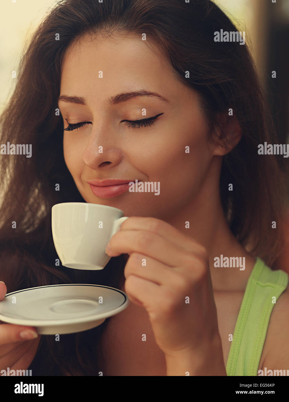 Beautiful happy woman drinking coffee with closed eye. Closeup vintage portrait - Stock Image