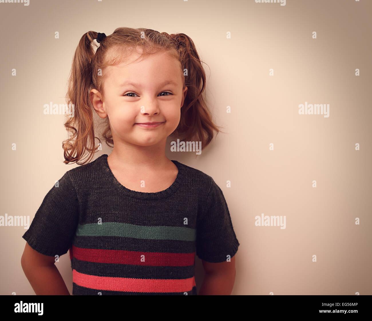 Happy grimacing kid girl looking on empty copy space background. Vintage portrait - Stock Image