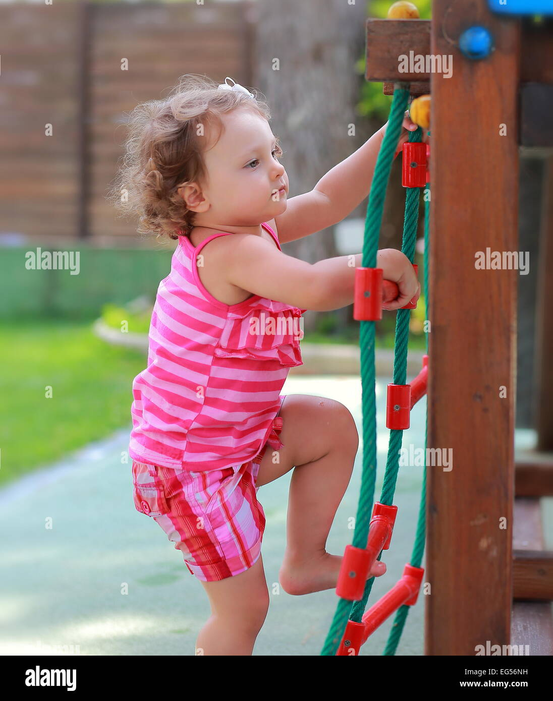 Small girl child climbing up on children activity ladder outdoors - Stock Image