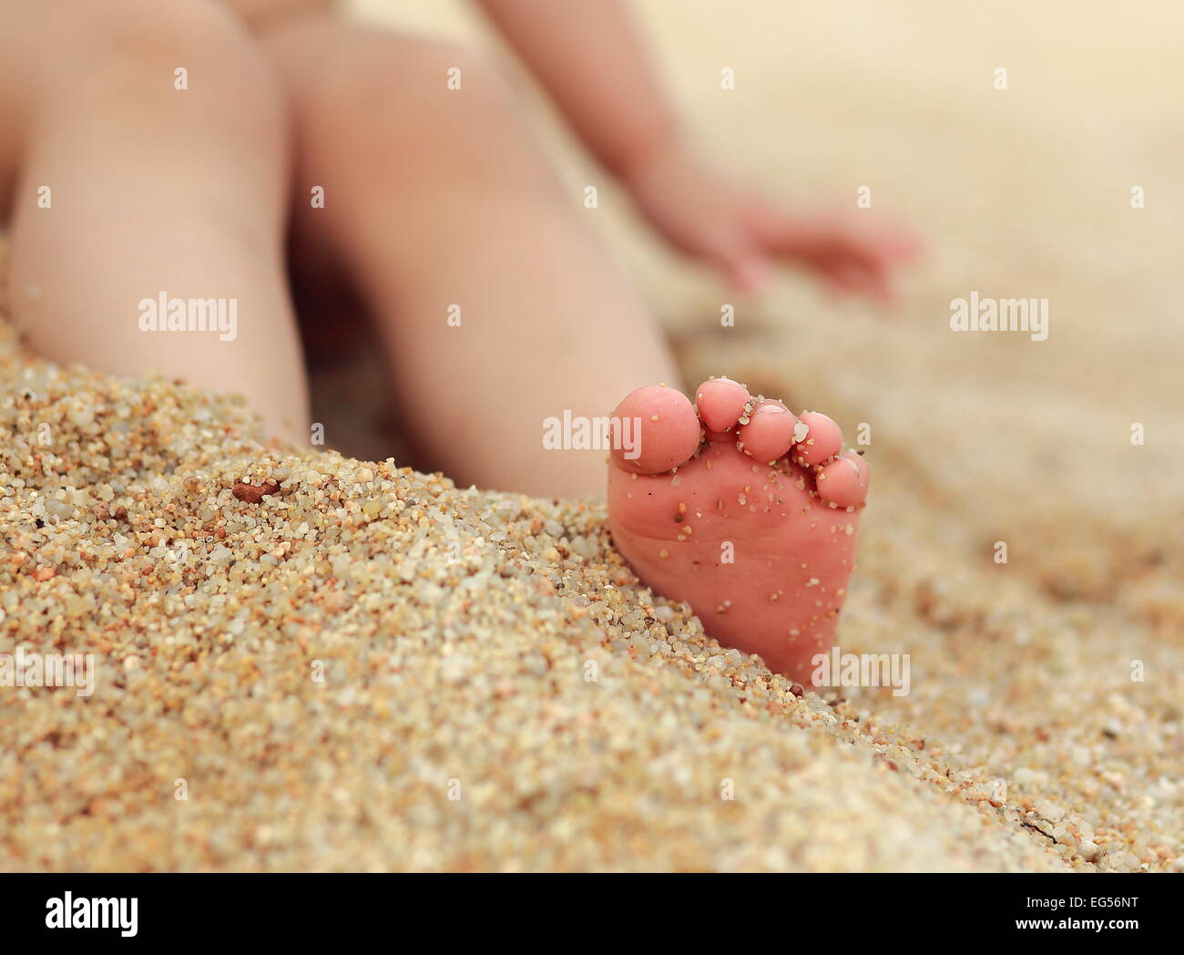Small baby feet on the sand background - Stock Image