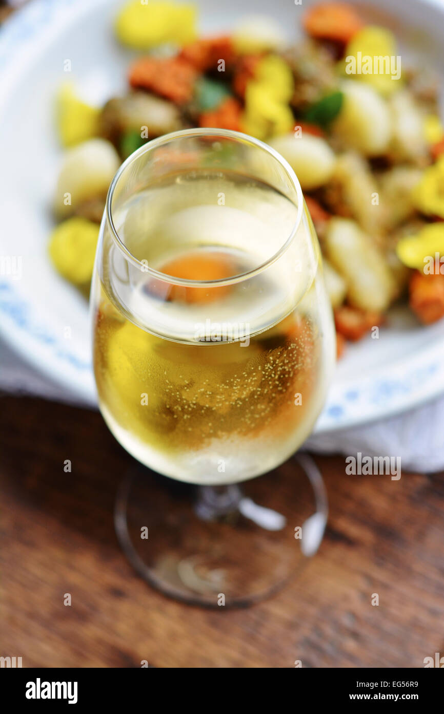 Glass of white wine in front of dish with gnocchi. Stock Photo