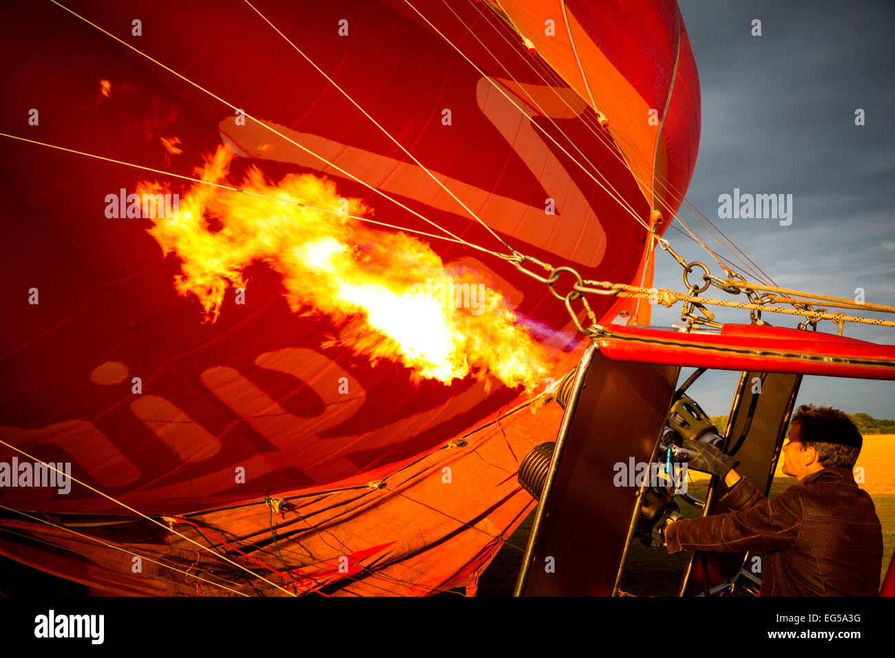 Man controlling gas burner flames inflating red hot air balloon, South Oxfordshire, England - Stock Image