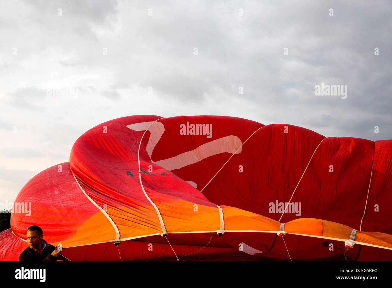 Man controlling billowing red hot air balloon, South Oxfordshire, England - Stock Image