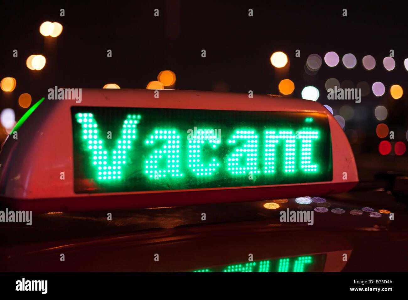 Vacant taxi sign illuminated at night - Stock Image