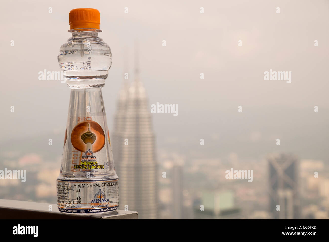 KL tower branded water bottle observation deck Kuala Lumpur Malaysia on a day with high humidity and hazy skies - Stock Image