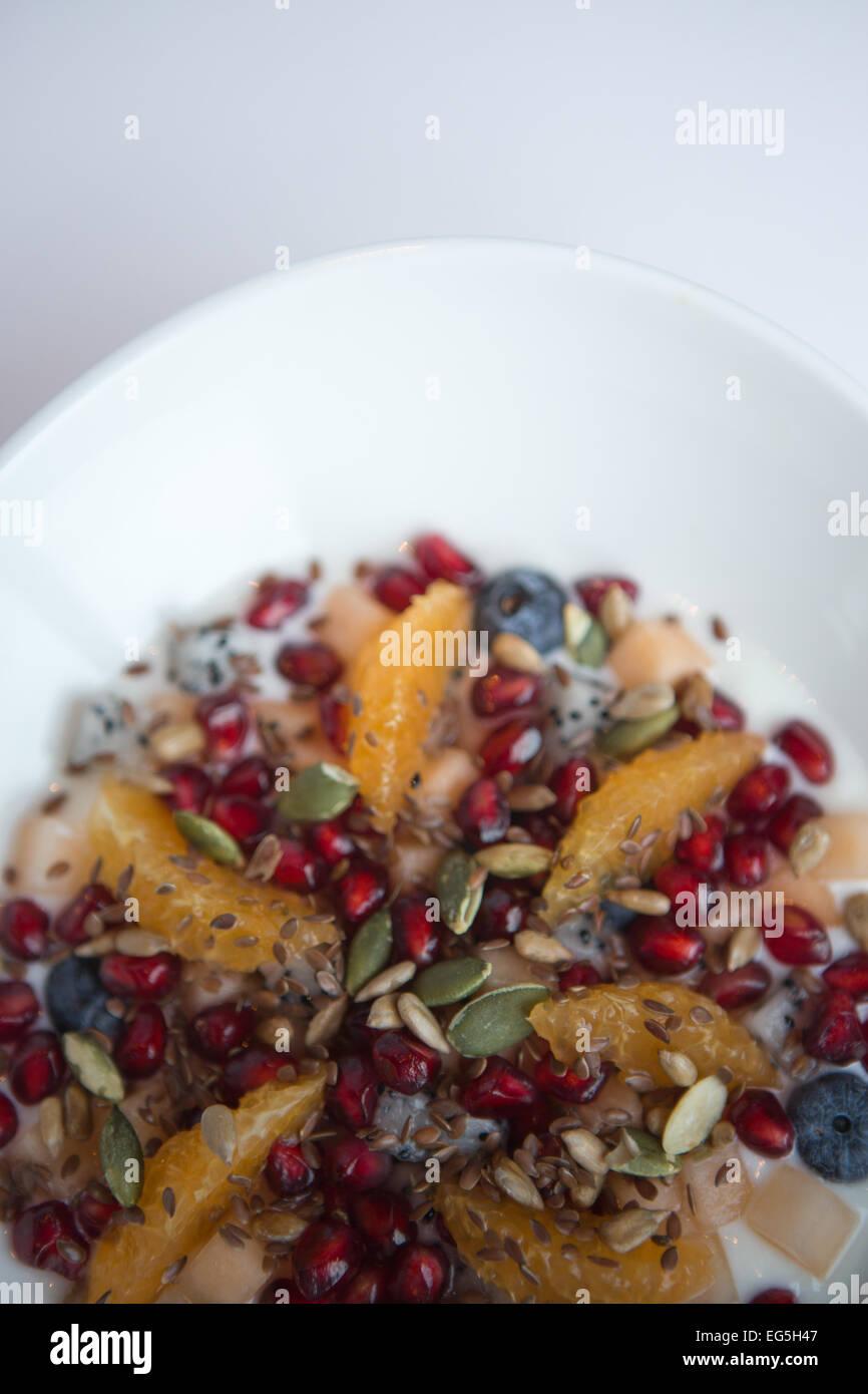 Orange segments, blueberries, pomegranate, dragon fruit, melon, pumpkin seeds, linseed, natural yogurt served in - Stock Image