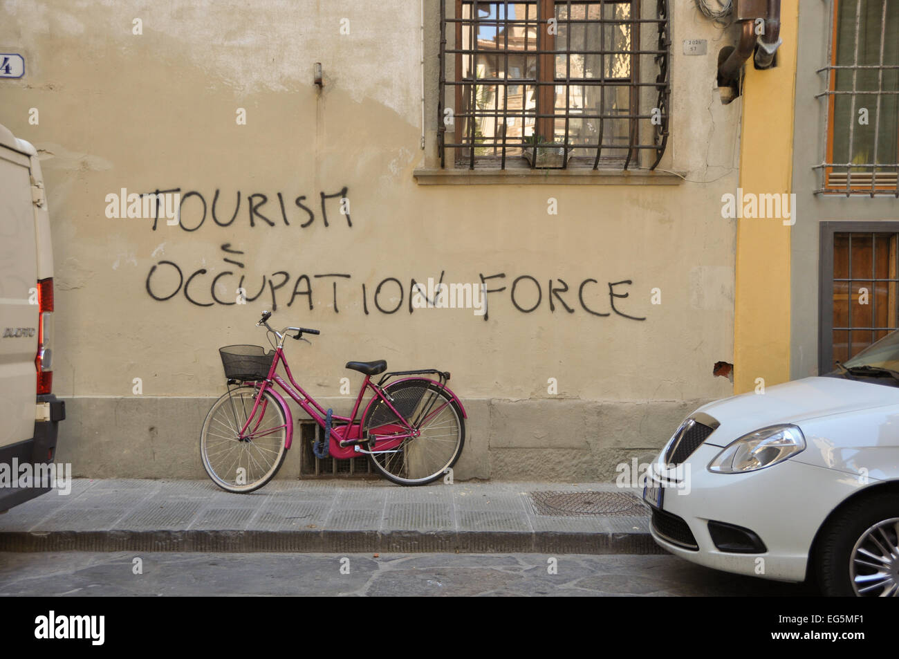 anti tourism graffiti on wall in Florence above pink bike - Italy - Stock Image