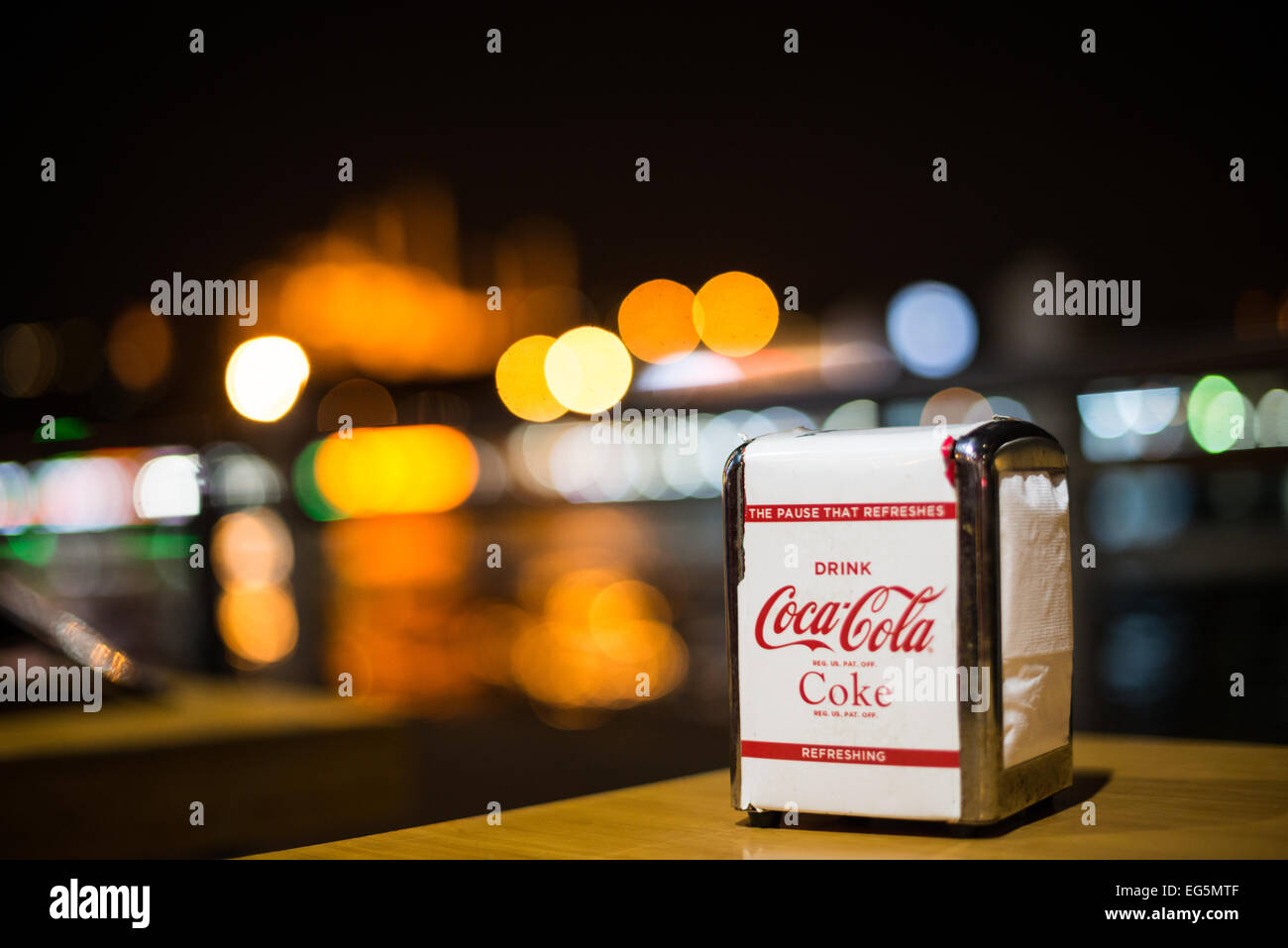 Branded Coca-Cola napkins in a dispenser on a table at a restaurant on the Galata Bridge in Istanbul, overlooking - Stock Image