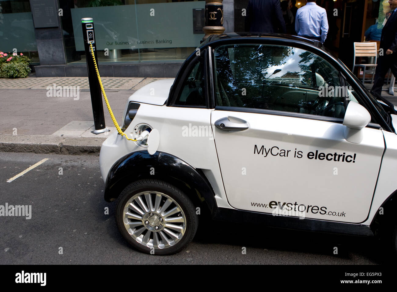 An Electric powered mini car parked in a battery charging bay in central London, England - Stock Image