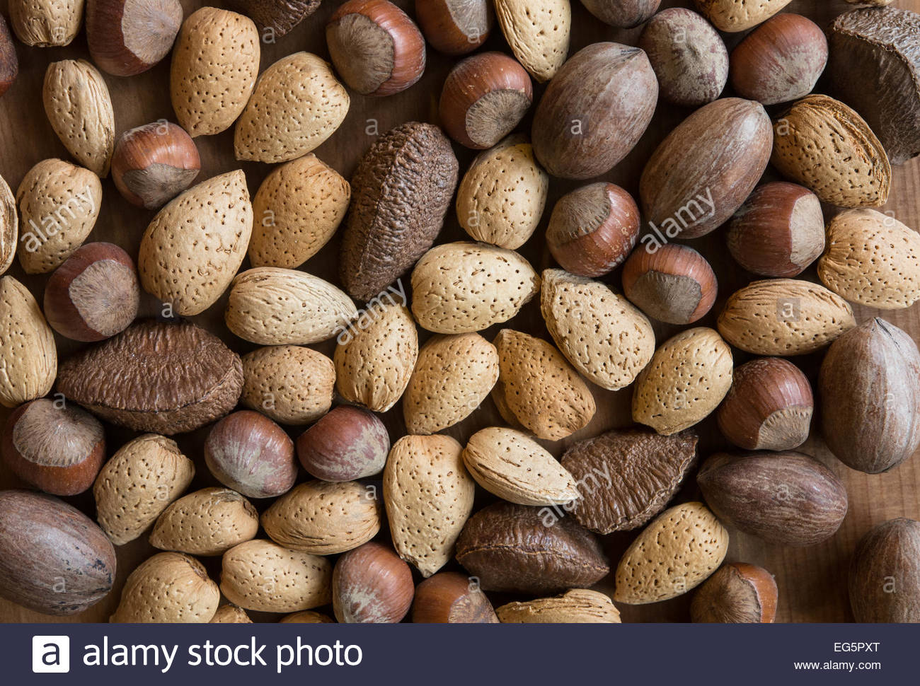 Mixed nuts in shells on wooden surface - Stock Image