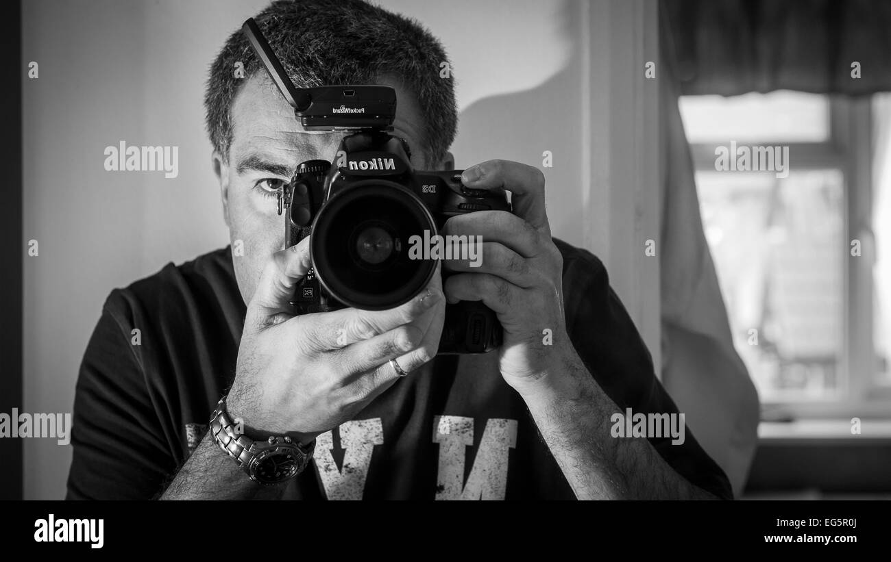 Mirror image of a man taking a photograph with a digital slr camera. - Stock Image
