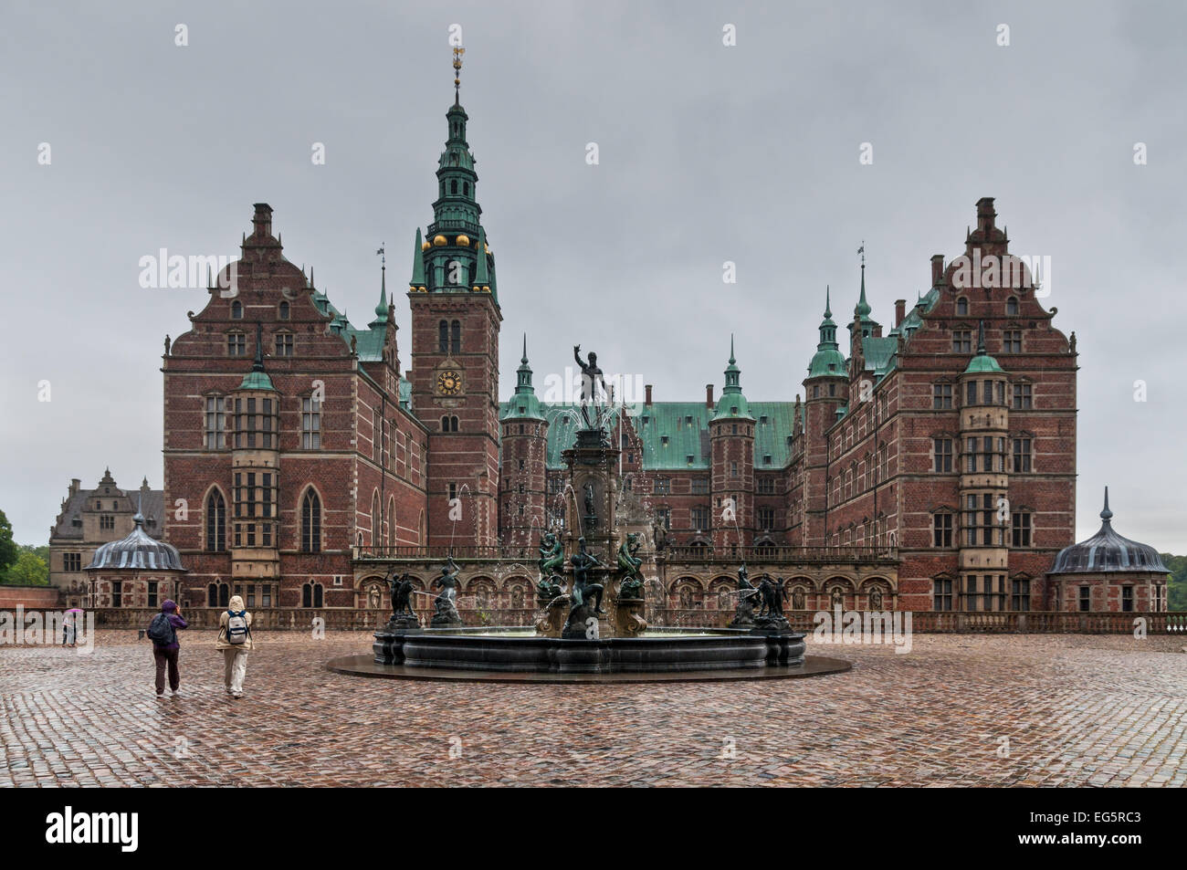 Tourists visiting the Frederiksborg palace and the baroque gardens in rainy weather. - Stock Image