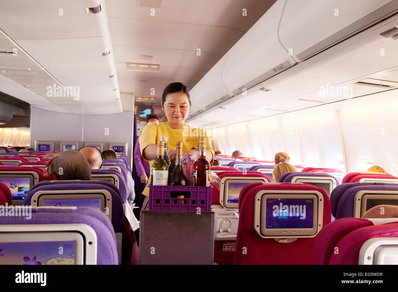 An air hostess serving drinks on a Thai Airways International flight from London to Bangkok - Stock Image