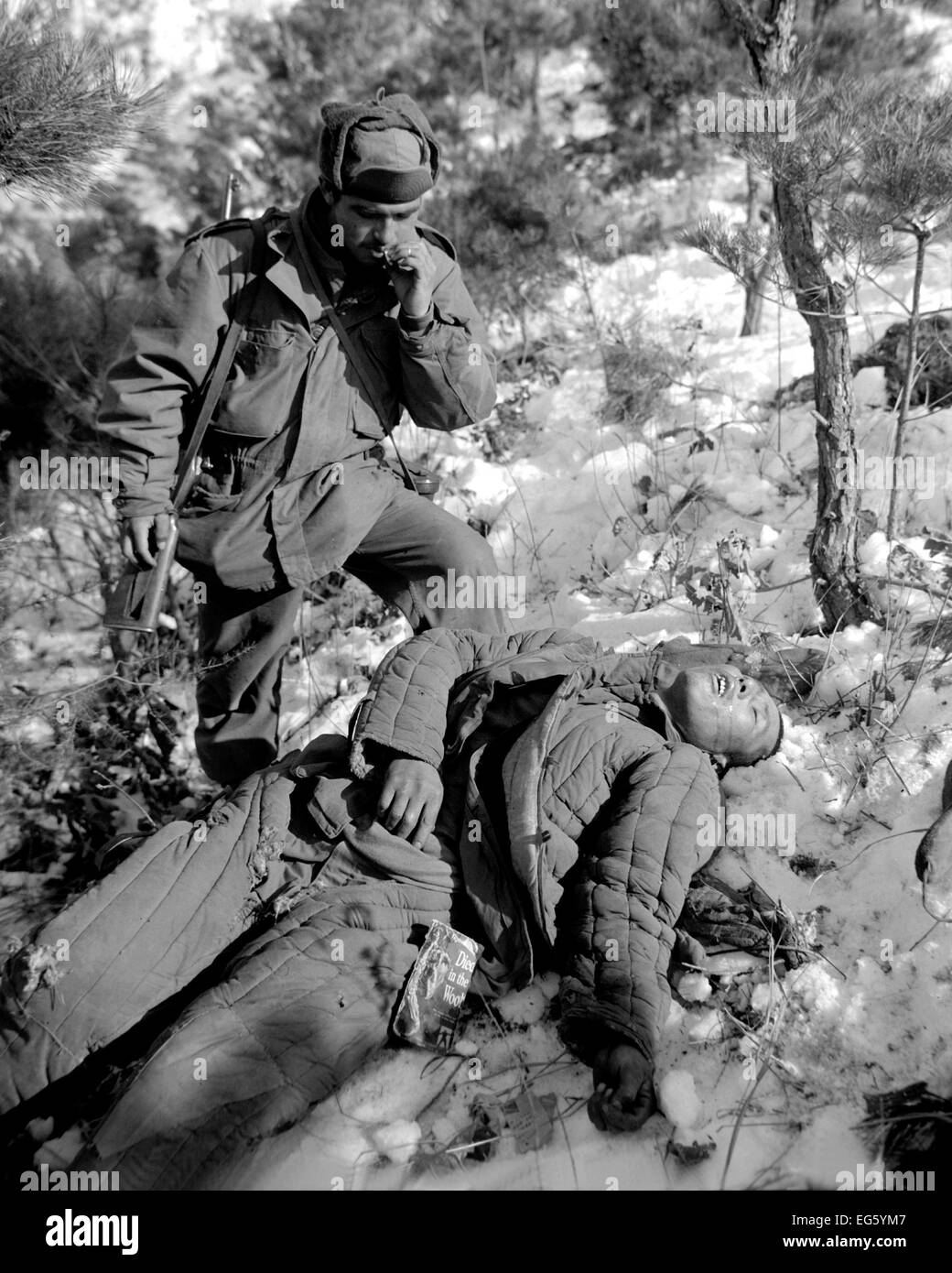 KOREAN CONFLICT:(1950-1953) American Sgt. Mike Chalooga  examines a dead Chinese Communist killed during the offensive - Stock Image
