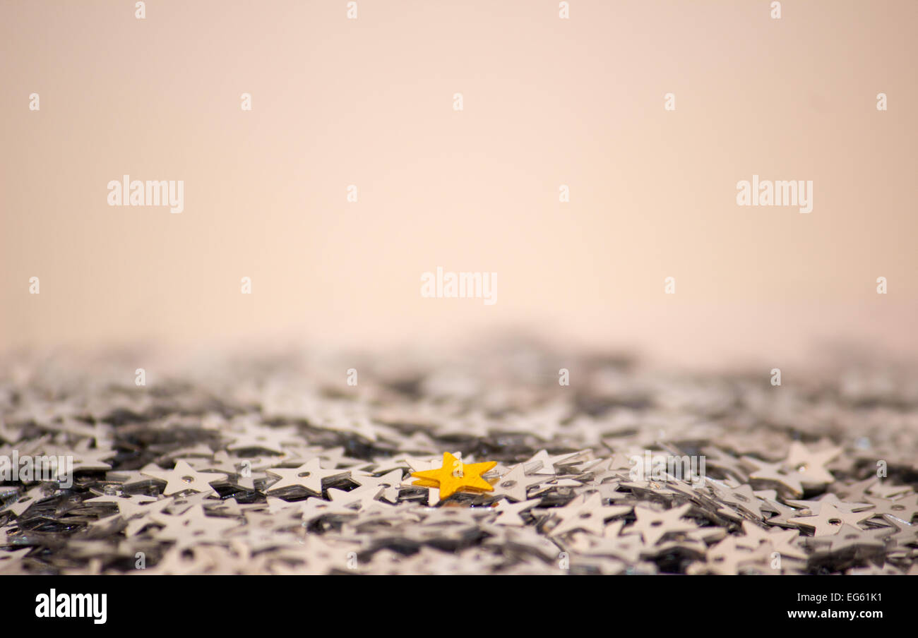 Gold star on sea of silver stars conveying individuality and standing out from the crowd - Stock Image