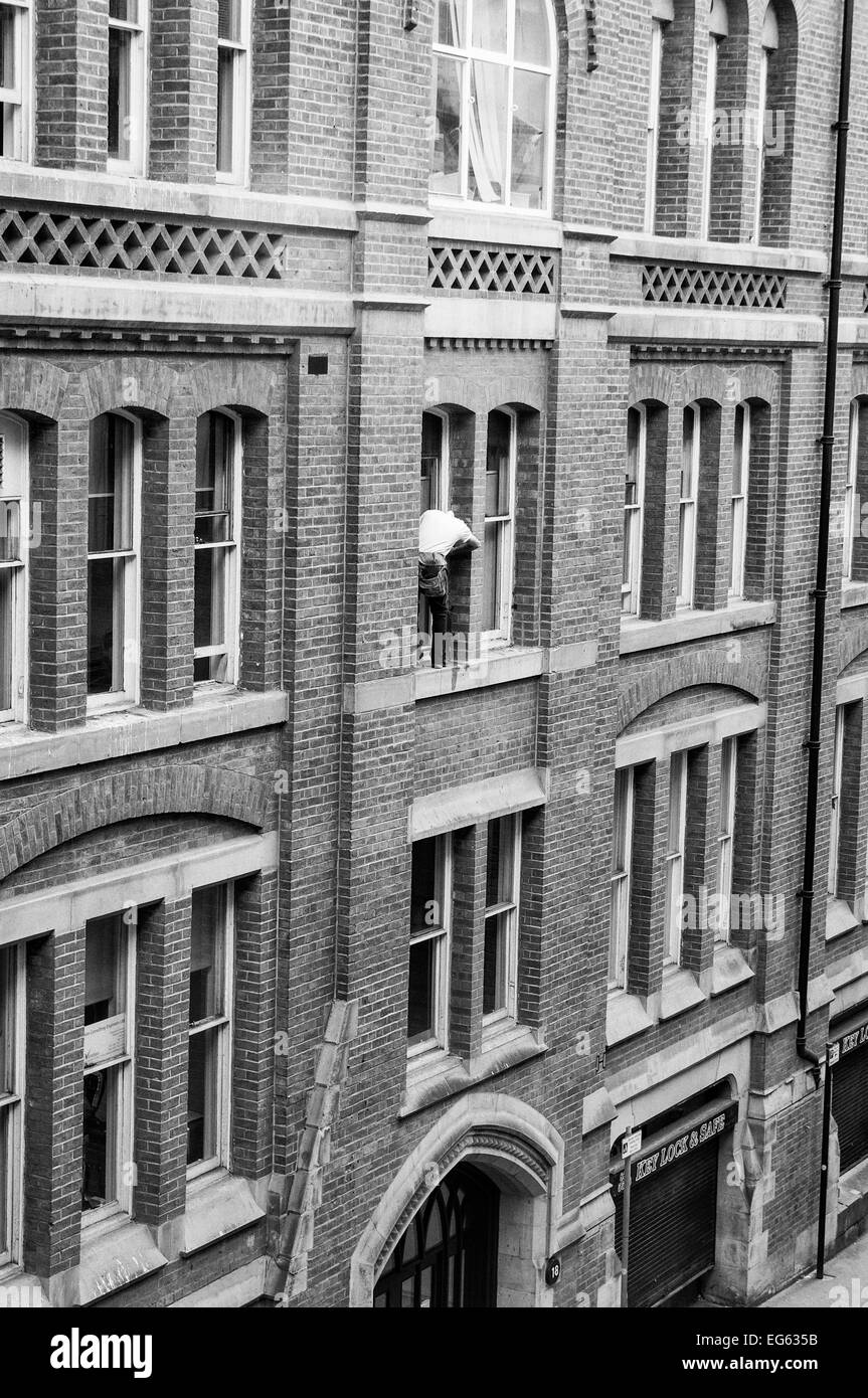 Window cleaner on very narrow ledge 3storeys up with no safety gear and man below oblivious to what is above him - Stock Image
