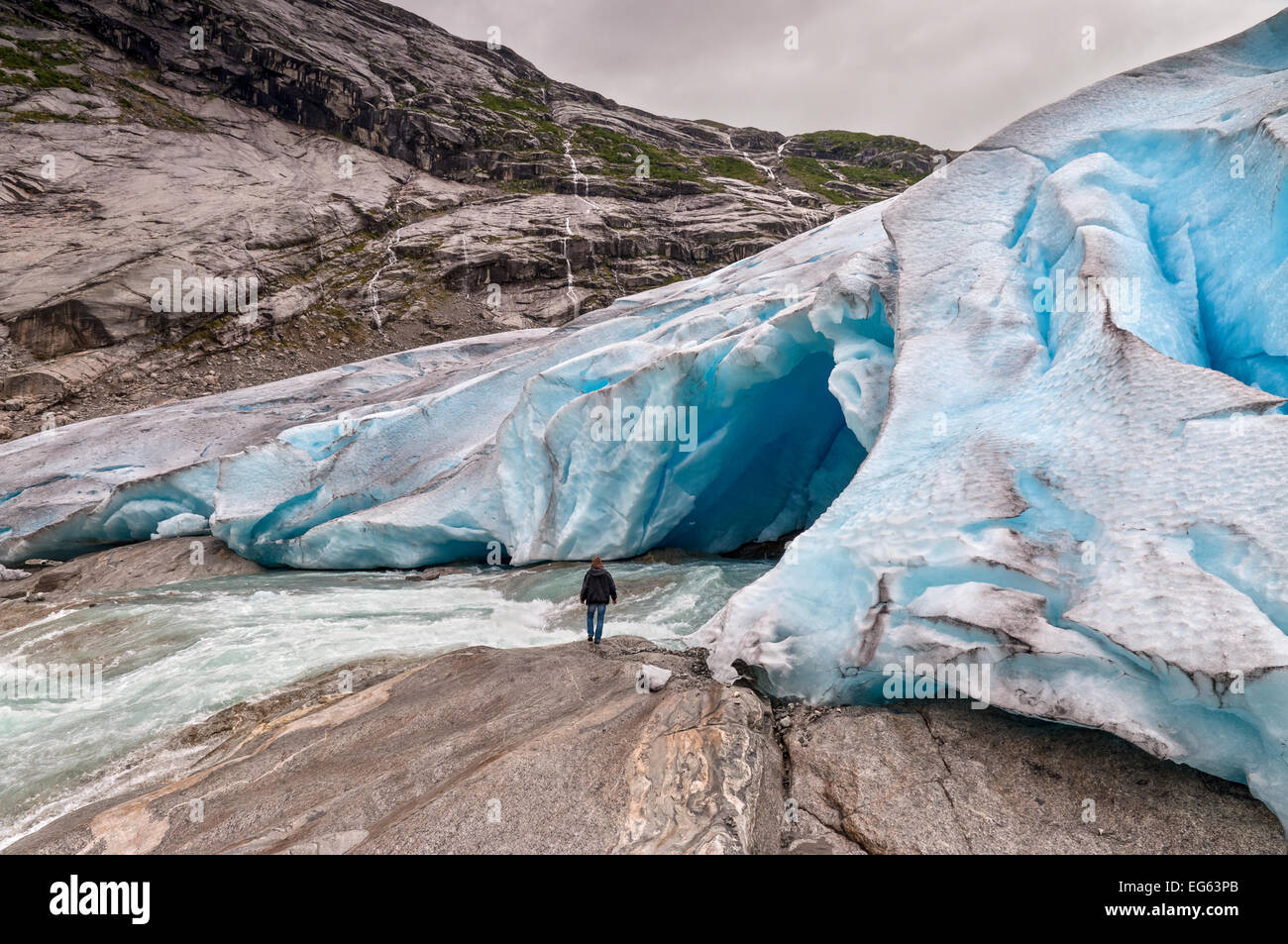 Jostedalsbreen glacier with the glacial river and man in Norway - melting because of Global warming. - Stock Image