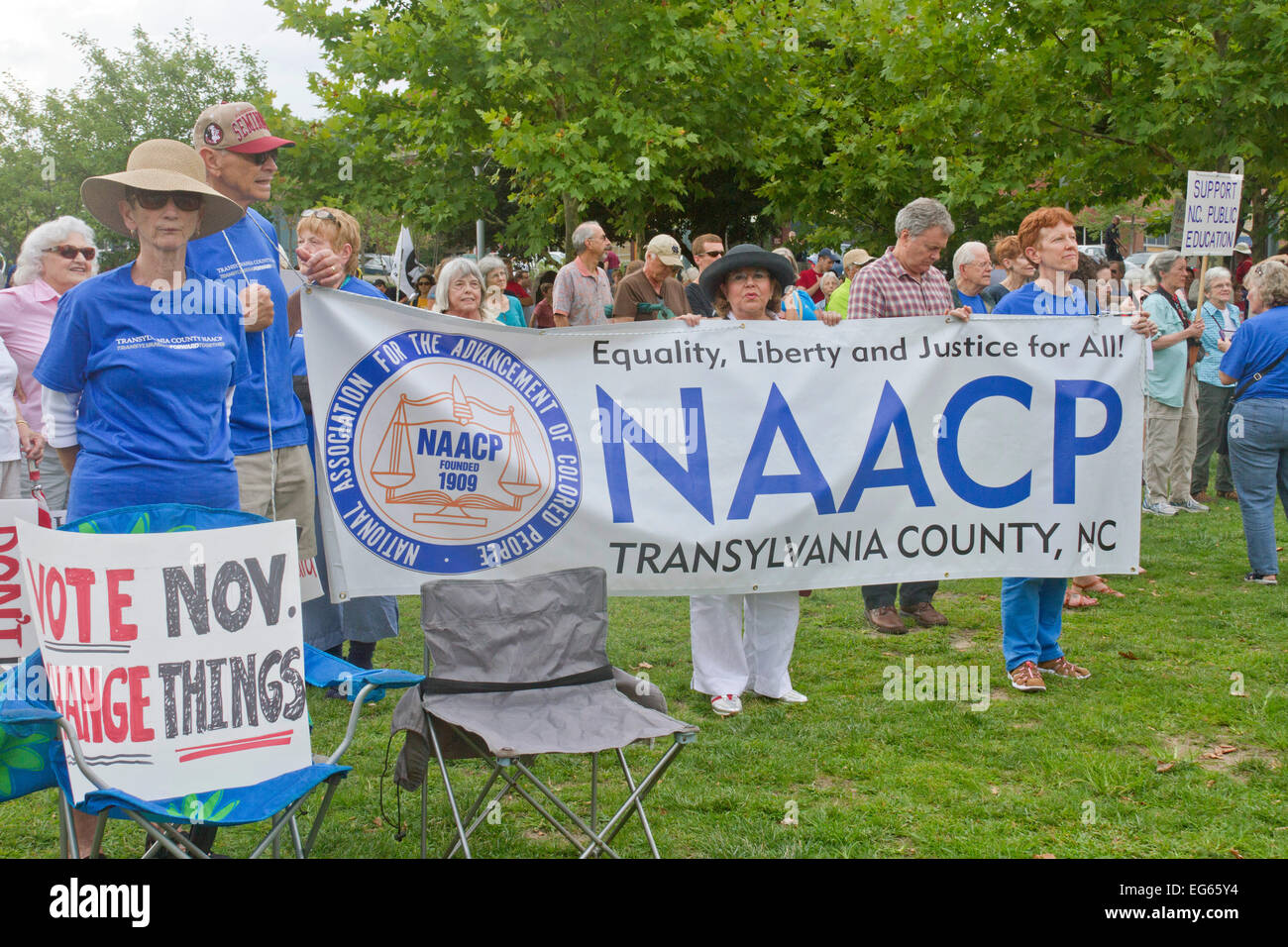 Crowd of mostly older caucasian people hold signs promoting the NAACP and voting at a Moral Monday rally - Stock Image