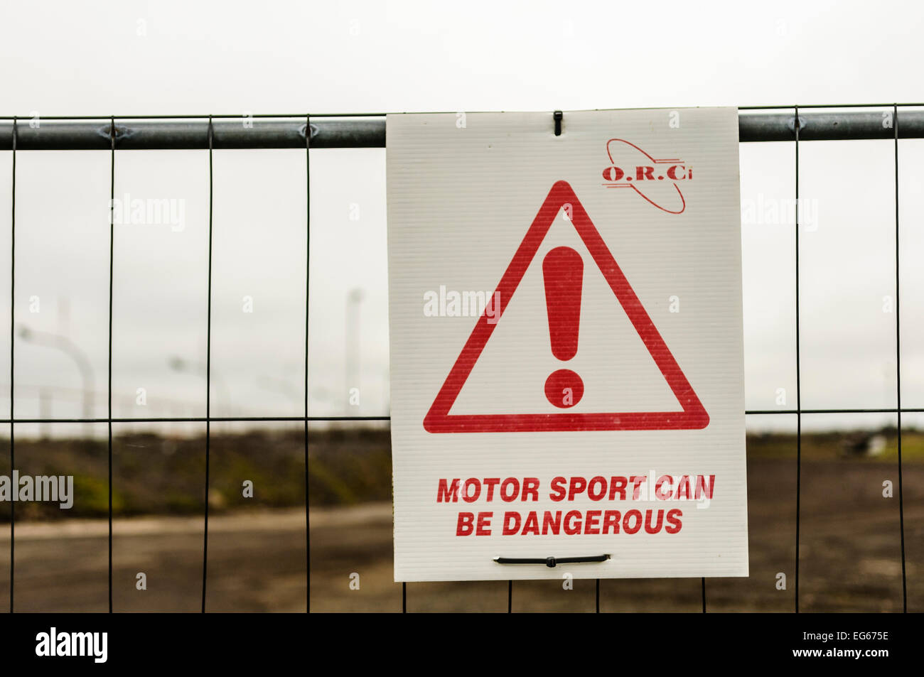 Sign at a race track advising the public that motor sport can be dangerous - Stock Image