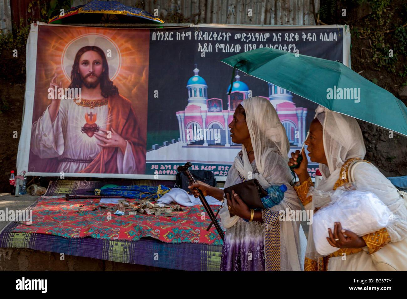 Two Pilgrims Walk Past A Portrait Of Jesus Christ, Lalibela, Ethiopia - Stock Image