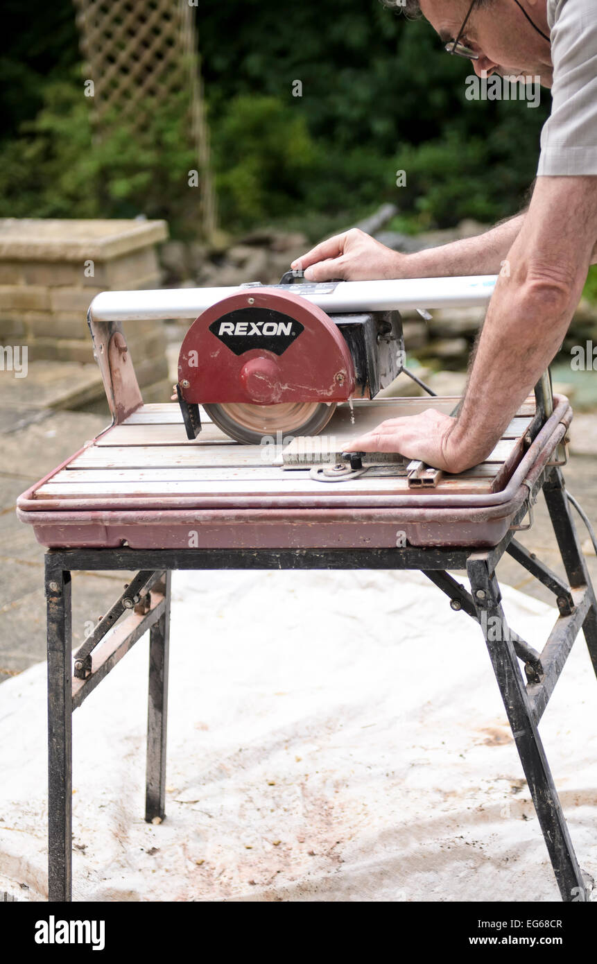 man using water cooled ceramic tile cutting machine release available - Stock Image