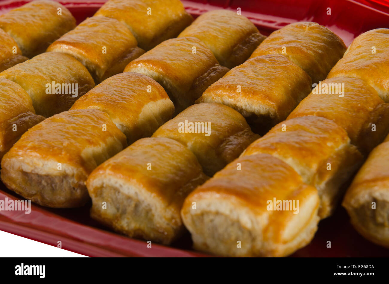 a plate of cooked sausage rolls - Stock Image