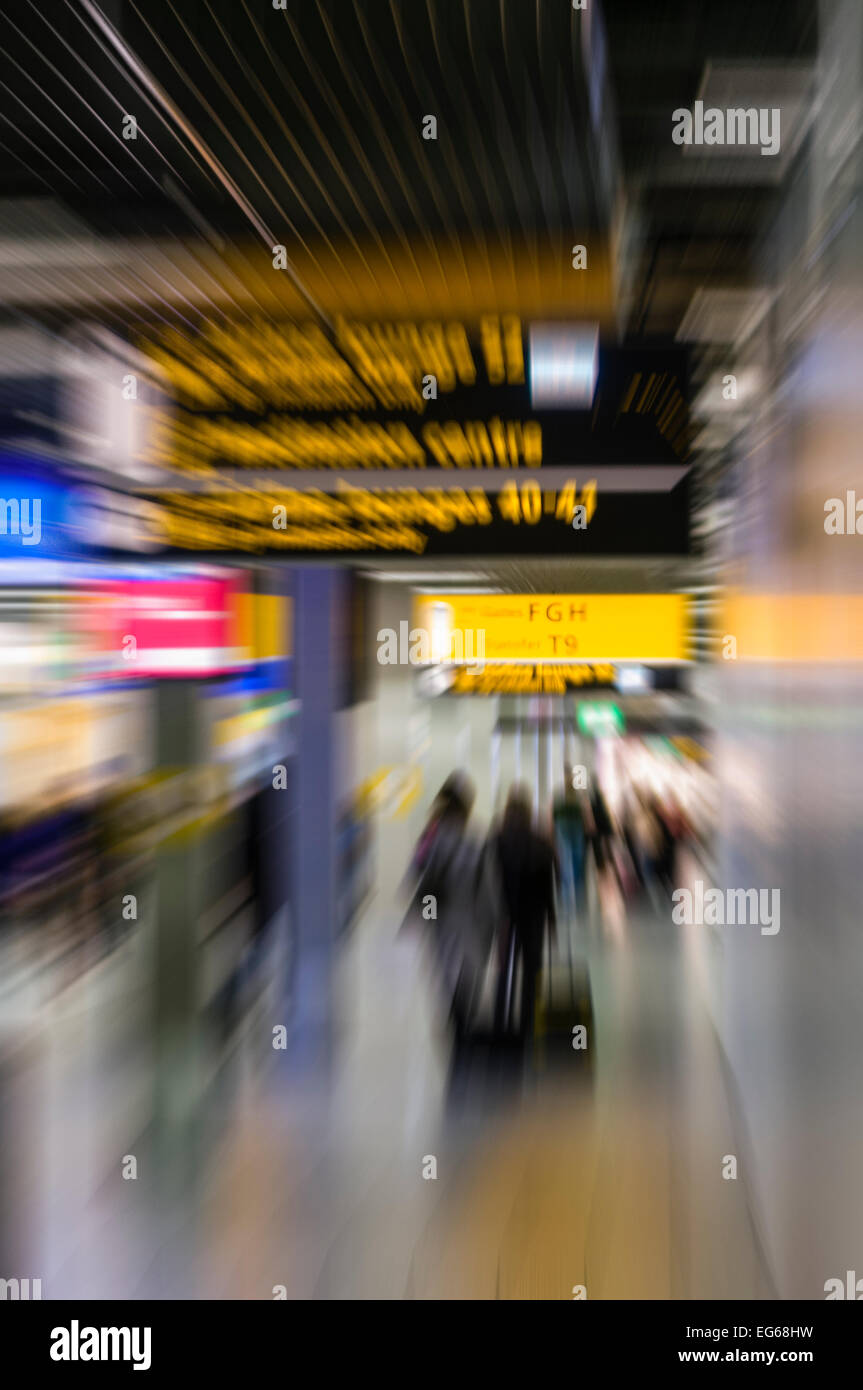 People walking towards the departure gates at an airport, blurred to show movement and speed. - Stock Image