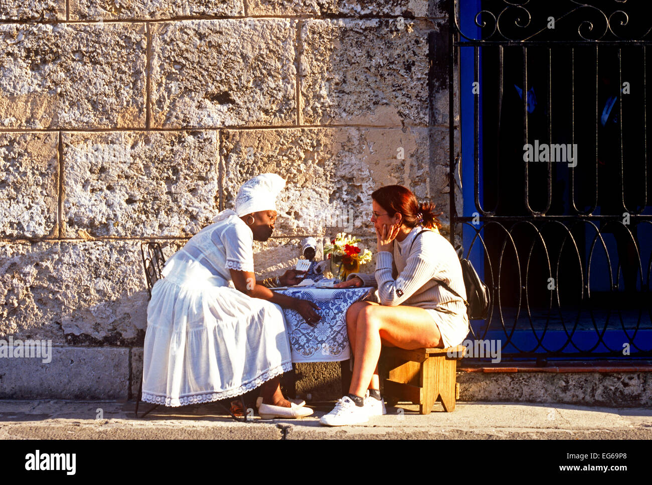 Voodoo Fortune Teller Giving A Reading to a Tourist in Havana Cuba - Stock Image