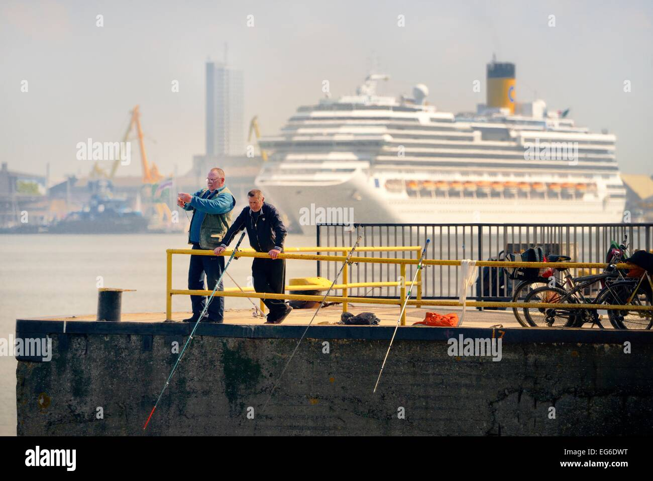 Klaipeda Lithuania. Fishing from the pier. Cruise ship Costa Pacifica and port facilities across navigation channel - Stock Image