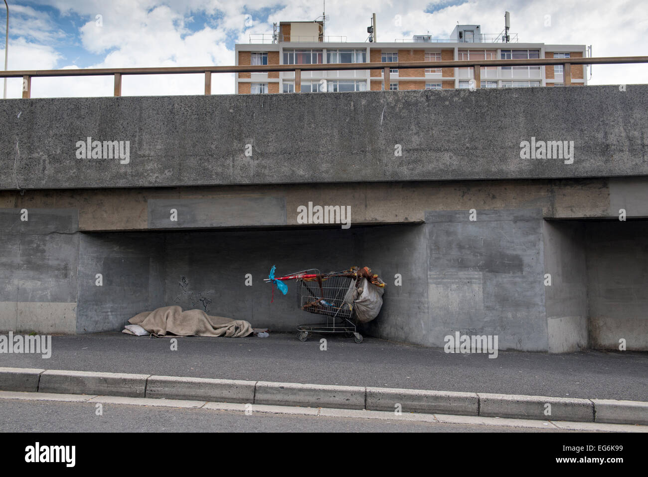 Sleeping homeless and shopping cart under a highway bridge, Cape Town, Western Cape, South Africa - Stock Image