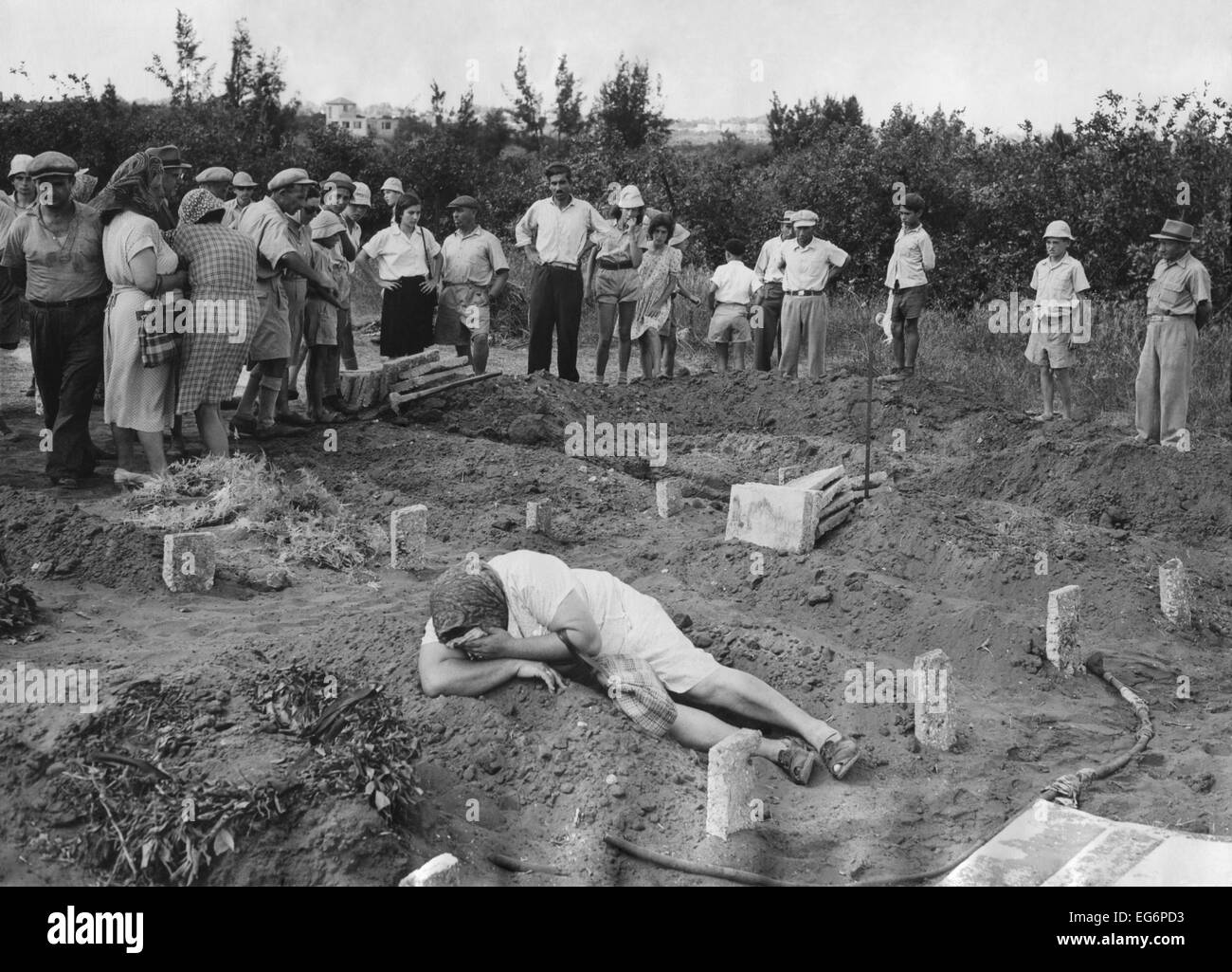A grief stricken mother lying on the grave of her Haganah soldier son. Near Tel Aviv, July 31, 1948. Over 6,000 Stock Photo