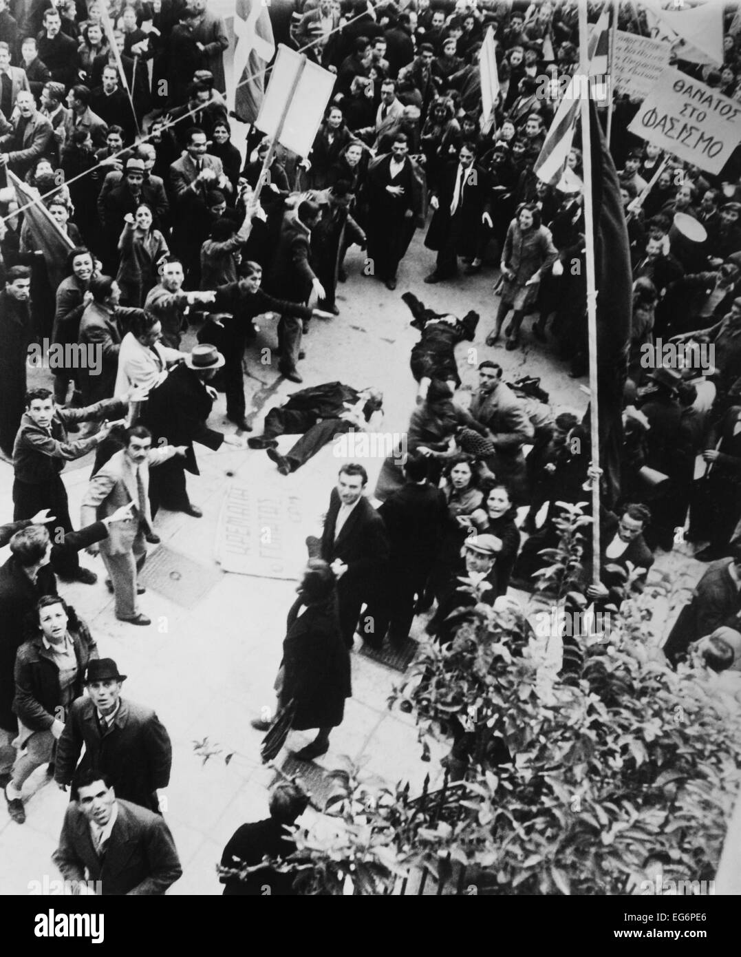 Crowd shouting and pointing towards a dead man and a woman lying in an Athens street. After liberation from the Stock Photo