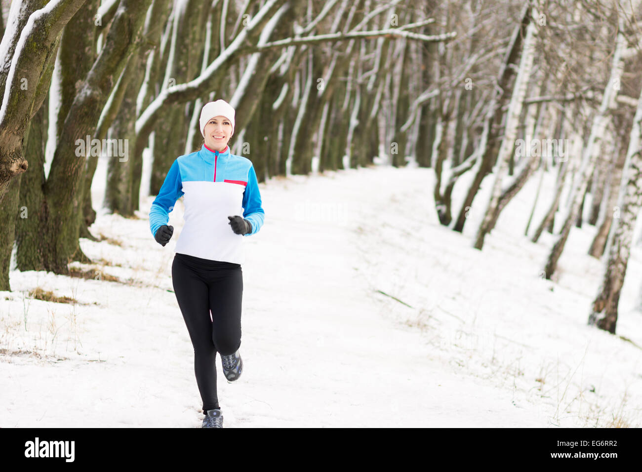 Cheerful young sport woman at winter outdoor activity. Smiling caucasian girl jogging in winter park - Stock Image