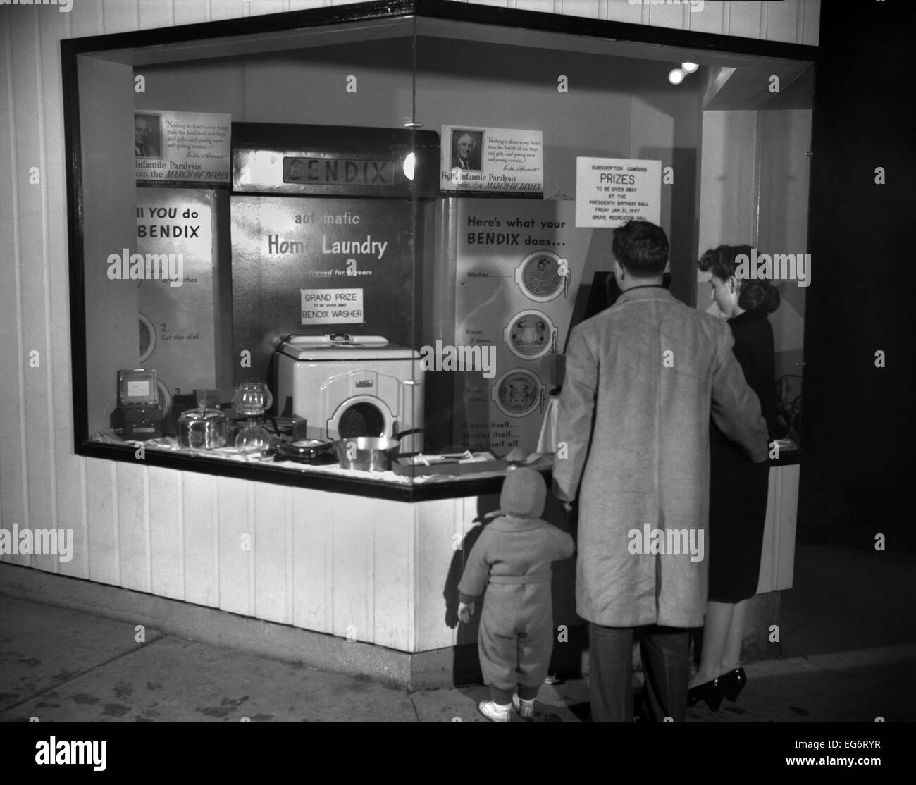Young family look at the Bendix Automatic Home Laundry. It will be given away by the Elks Club at the President's - Stock Image